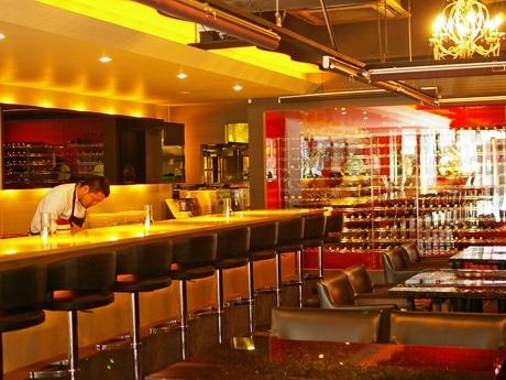 ラックにワインが並ぶ「レクランドゥデリス」店内。バーカウンター越しにシェフがスイーツを作る。