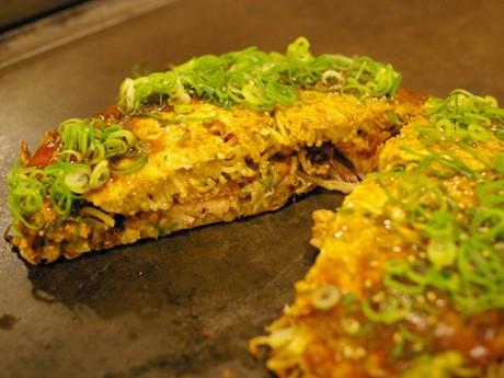 肉・卵・生イカ・生エビ・イカ天が入った「長田屋焼」。お好み焼きの上にはたっぷりのネギと黄卵が乗る。