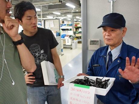 東京で開催された「地域魅力発見バスツアー」で訪問した企業の工場で話を聞く参加者