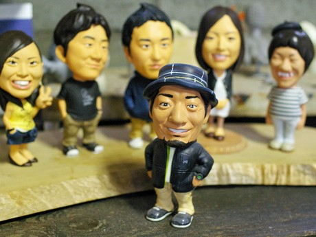 依頼者の写真を見ながら制作するポートレート人形。中央は制作者の田中秀樹さん。