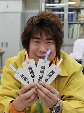 レッサーパンダとアフリカゾウのふんを使った2種類のしおりを手に持つ田邊さん