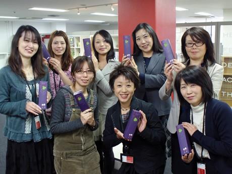 ホワイトチョコレートでコーティングしたJewel(ジュエル)を手に持つソラアサービスのスタッフ。写真中央は牛来千鶴社長。