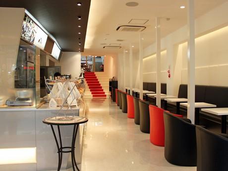 白を基調に赤や黒でスタイリッシュにまとめた「CafeMランド」店内