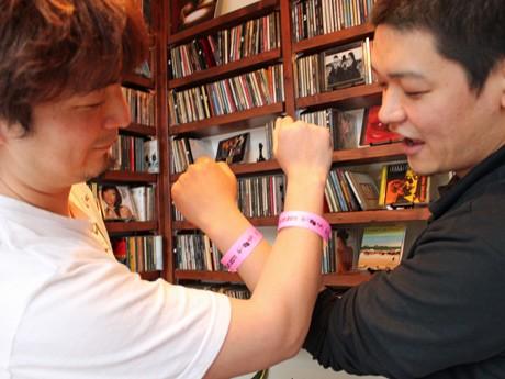 リストバンド式のチケットを手首に巻く「笑廣會(しょうこうかい)」メンバーの奥原考徳さん(左)と迫田さん