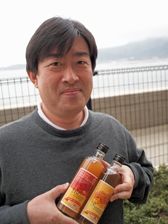 宮島を背景にフルーツビールを手に持つ有本さん