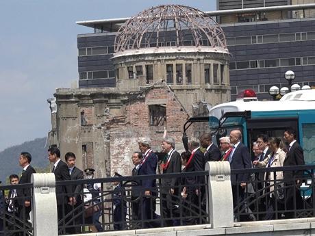 急きょ、原爆ドームを見学した外相。首には各国の国旗の色をモチーフに千羽鶴で作ったレイを下げている