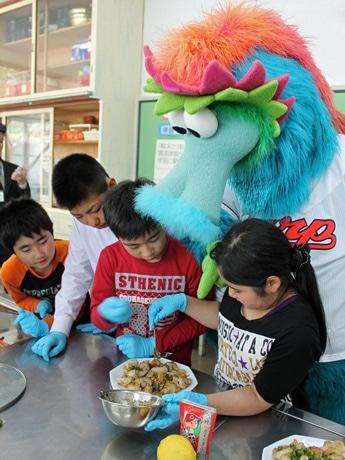 3~4人のグループに分かれて調理する児童たち