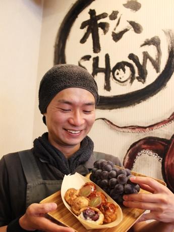県産ピオーネを1粒丸ごと使った「広島ピオーネたこ焼き」を持つ店主の松村さん