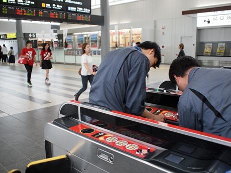 JR広島駅の自動改札機にシールを貼りつける作業スタッフ