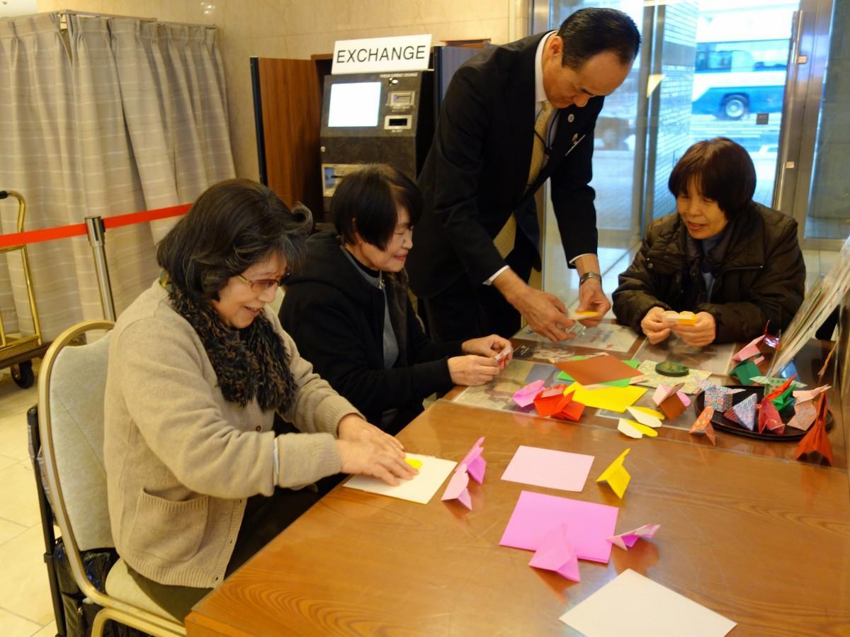 隣りに座った人と会話しながら折り紙を折る参加者