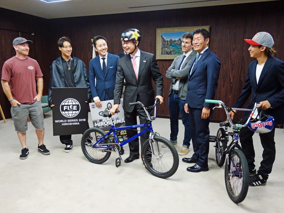 大会前に湯崎広島県知事を訪ねた日本アーバンスポーツ支援協議会の渡辺会長や選手たち。湯崎知事がBMXのヘルメットを着用するシーンも。