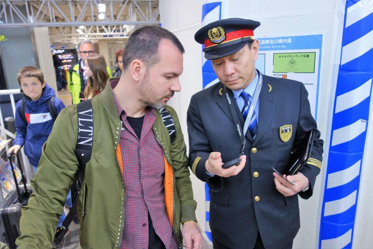 新幹線改札口でポケトークを使って観光案内を行うJR職員