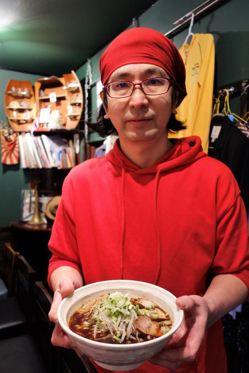 ラーメン店「稟麺」を切り盛りする安部宏さん。手に持つラーメンは、「富山ブラック」をベースにアレンジした「横川ニューブラック」。