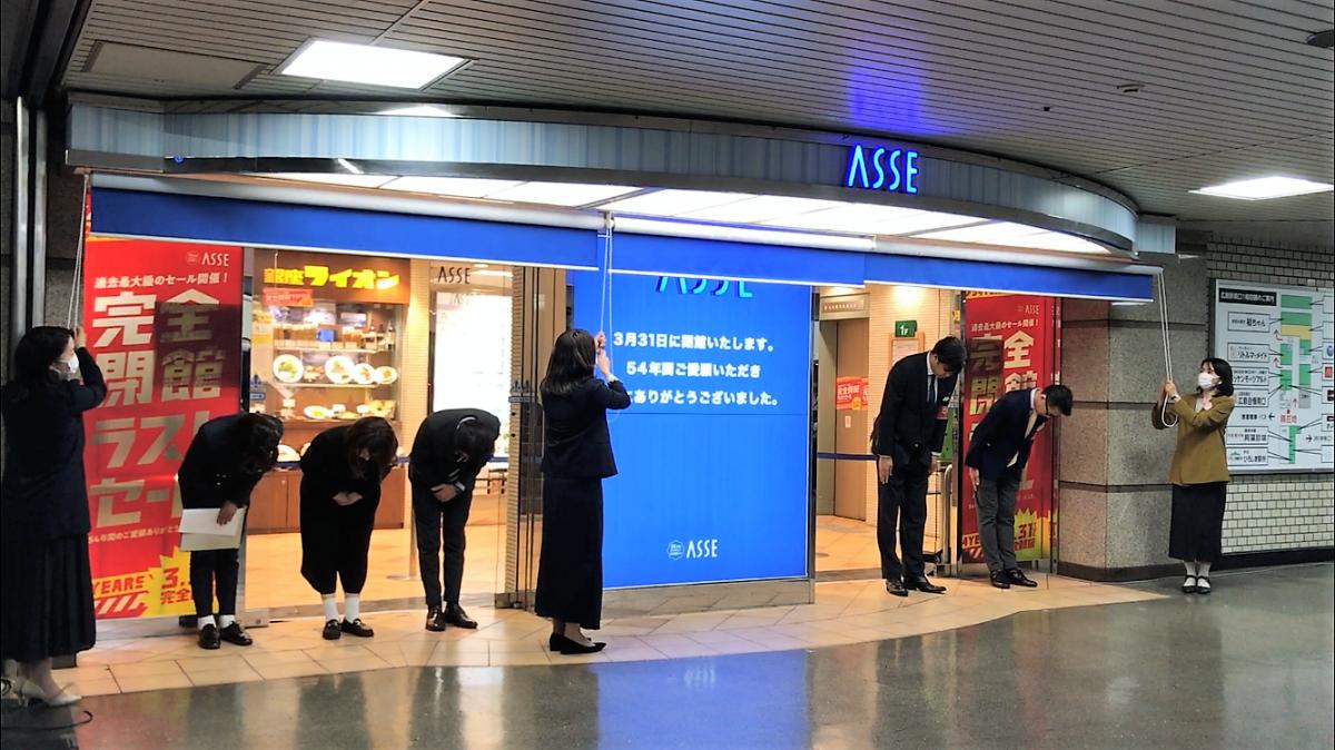 閉館セレモニー後、ロールスクリーンの前でお辞儀する藤岡社長(写真右から3人目)と中国SC開発のスタッフ