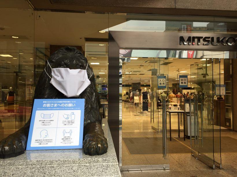 広島三越のライオン像もスタッフ手製のマスクを着用し、感染予防を呼び掛ける看板を掲げる。