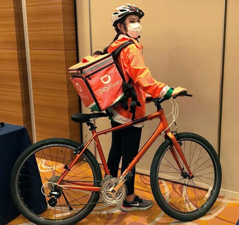 オレンジ色の上着と宅配リュックが印象的な「DiDiフード」の配達員