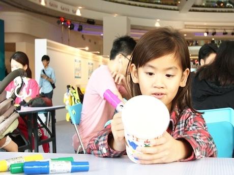 自分だけのカップヌードルのパッケージに絵をかく香港の子ども