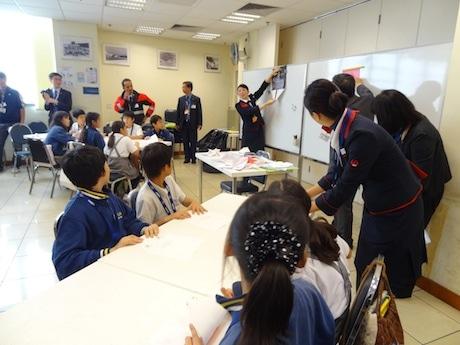 客室乗務員の担当者から紙飛行機の作り方を習う日本人学校の児童