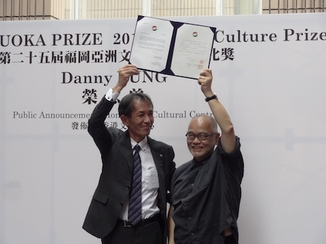 賞状を掲げ、受賞の喜びを表すダニー・ユンさん