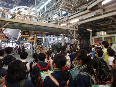 整備工場で機体の大きさに胸を躍らす児童