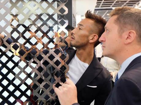 日本酒セラーの扉を開き、自ら熱心に説明をする中田英寿さん