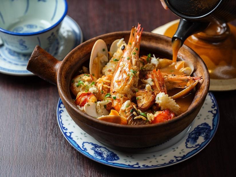8つの海鮮をのせ煮込んだ米にロブスターソースをかけて提供