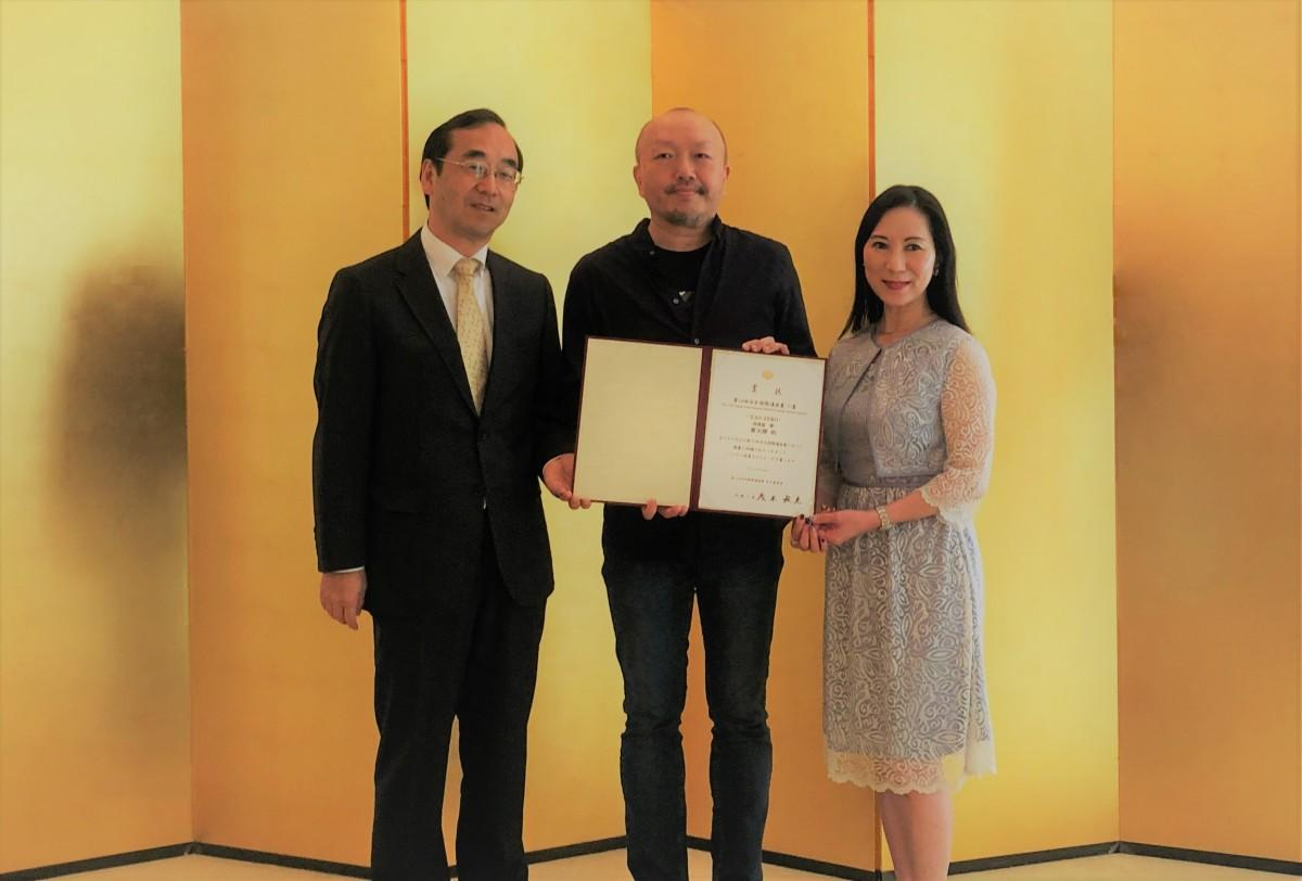 和田大使兼総領事から表彰状を受け取った麥天傑(Mr.Tin Kit Mark)さん(中央)