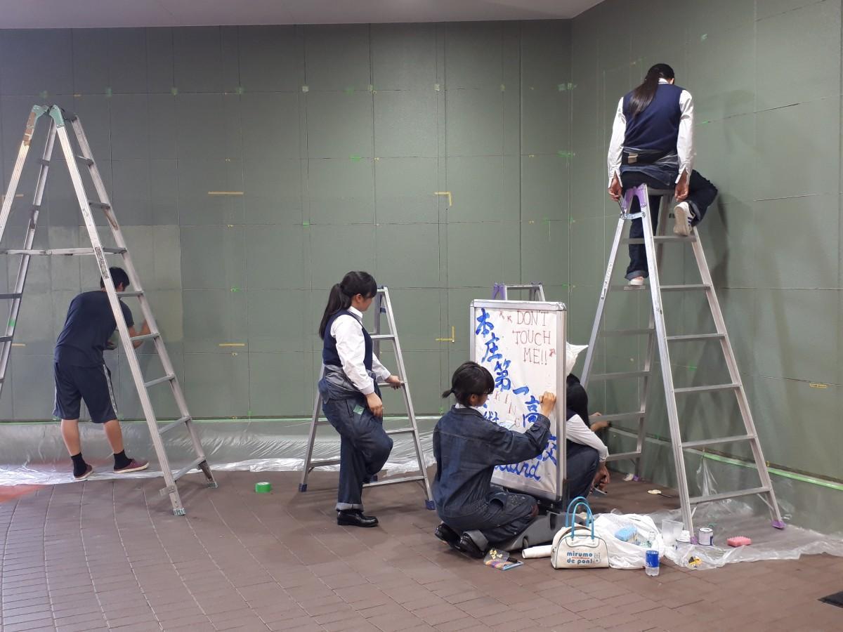 脚立を用いて外壁に印を付ける美術部所属の高校生