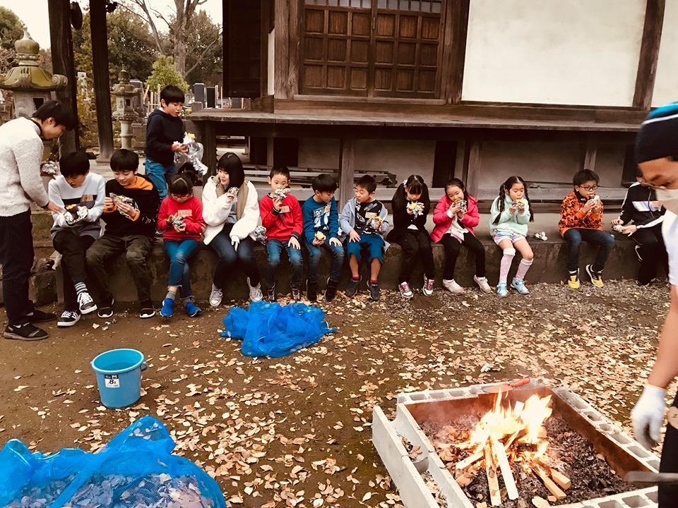 落ち葉を焼いて作った焼き芋を食べる「冬休み寺子屋体験」参加の児童