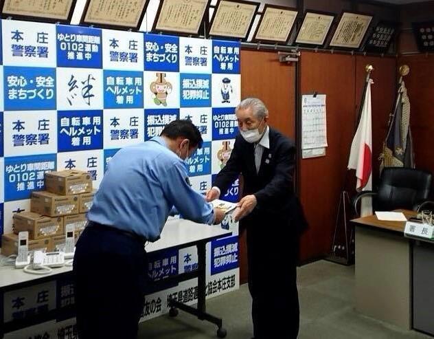 本庄警察署で青木正人署長(左)に目録を手渡す高橋福八会長