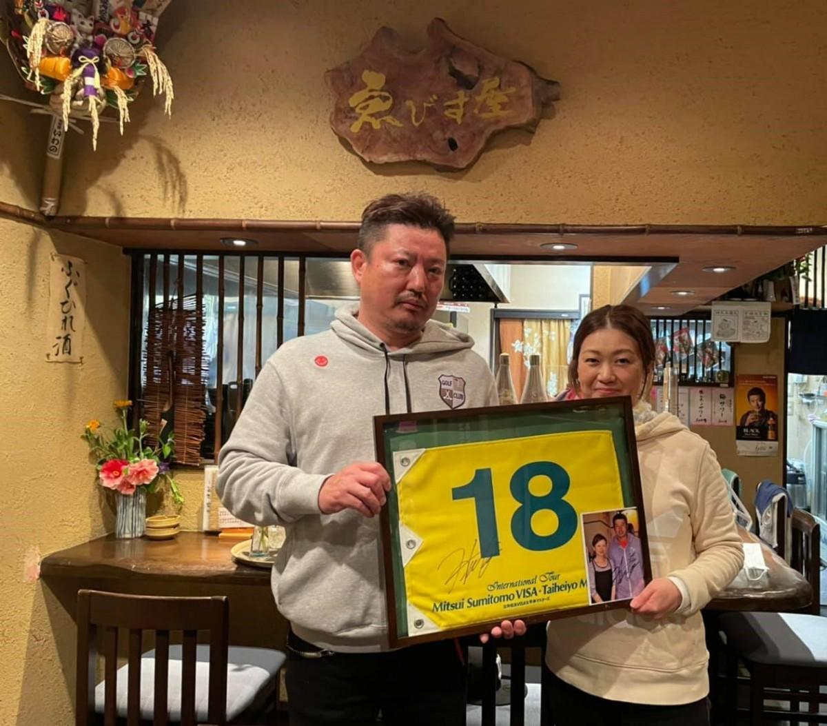 松山選手サイン入りのフラッグと写真を持つ居酒屋「ゑびす屋」の大澤夫妻