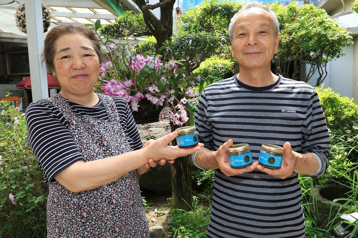 ちりめんアヒージョを手にする高橋水産の高橋建生社長(右)と留美子夫人