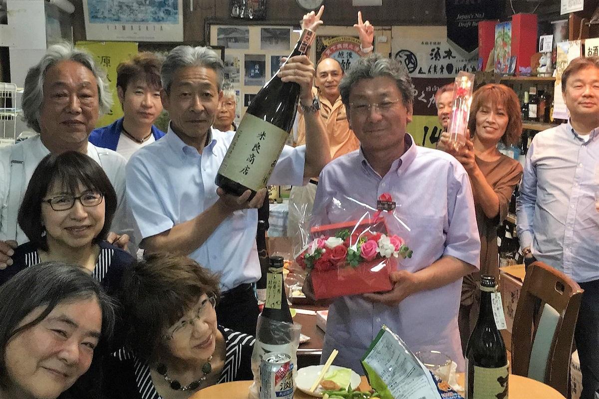 1周年を祝う角打ちの客と花をもらった米良さん(中央右)