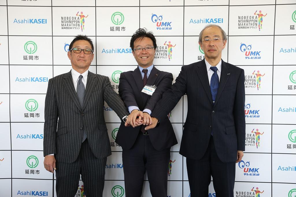 大会の成功に向けて握手を交わす読谷山市長(真ん中)ら