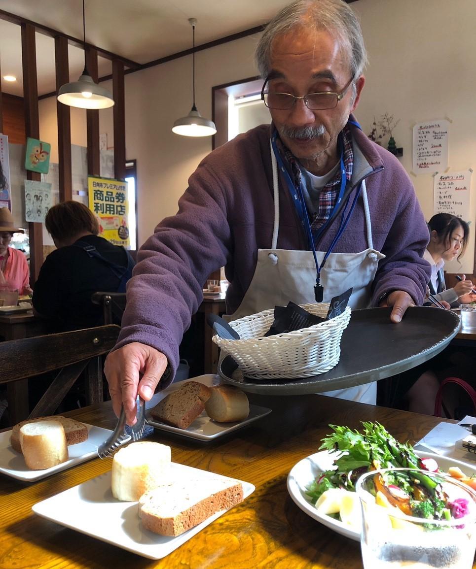 客にパンを提供する70代男性