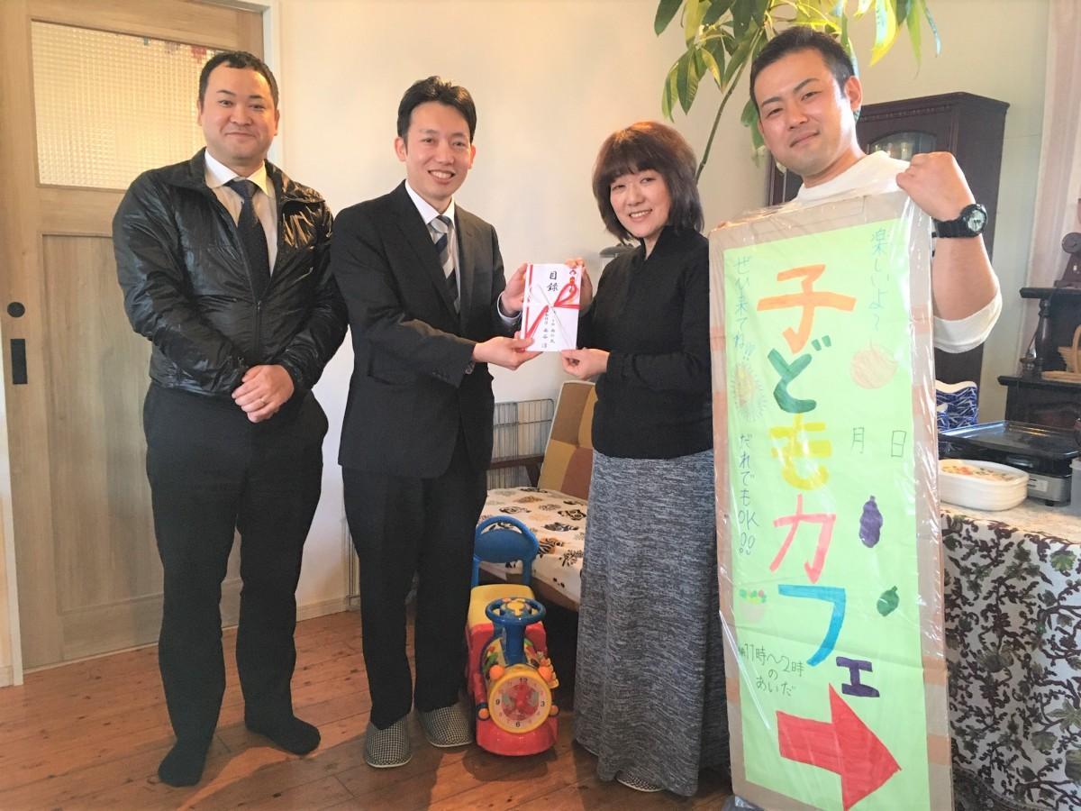 子どもカフェを運営する堀さん親子(右)へ寄付金を渡す西の丸の石崎さん(左から2番目)