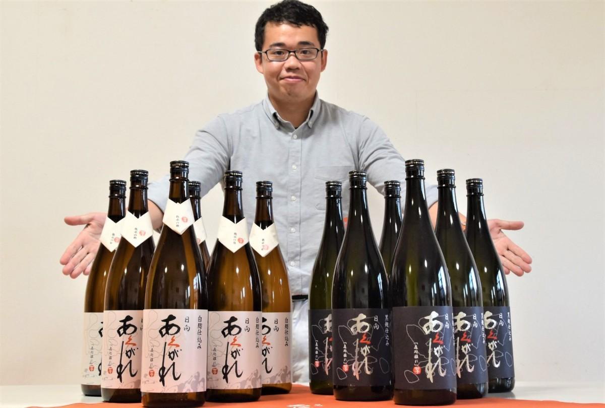 最優秀賞に贈られる焼酎を前に笑顔を見せる杜氏の山本豊文さん