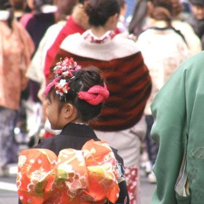 楽しそうに神楽坂を練り歩く参加者たち。沿道の観光客がデジカメ撮影する姿も