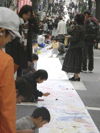 坂道に敷かれたロール紙の両サイドには描く人以外に多くの見物者の姿も