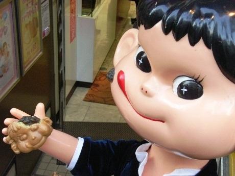 神楽坂名物「ペコちゃん焼」が今年で発売40周年を迎える。店頭に立つペコちゃん人形の手にも「ペコちゃん焼」が。