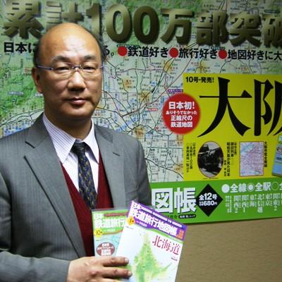 シリーズ累計100万部突破のポスターを背にする田中比呂之さん。