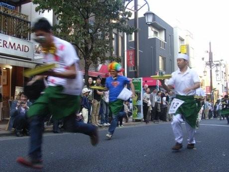 神楽坂で「ギャルソンレース」が開催された。沿道の観客の声援を受け、ゴールを目指す出場者ら。