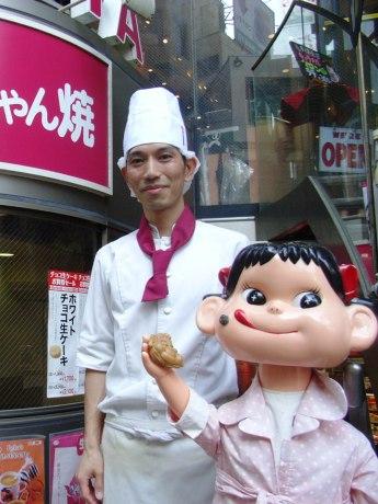 「ペコちゃん焼」の販売から40周年を迎えた不二家飯田橋神楽坂店の平松潮店長と看板娘・ペコちゃん。ペコちゃんの手には「ペコちゃん焼」が。