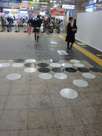 JR市ケ谷駅構内改札付近の床に設置された「黒先長生」のモザイクアート