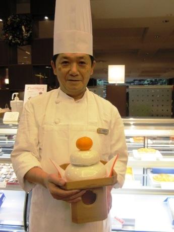 「オレンジケーキの鏡餅」を持つシェフパティシエ・間野目裕行さん(商品に三方、みかんは含まれない)