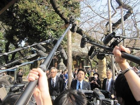 大勢の報道陣に囲まれて桜の開花を発表する気象庁職員
