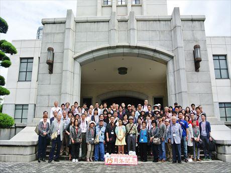 「市ヶ谷記念館」前で記念撮影を行う約100人の参加者