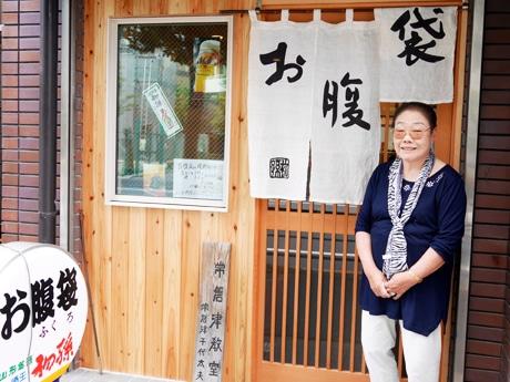 店先に立つおかみの高橋和子さん。のれんの文字は店の名付け親である5代目柳家小さん師匠によるもの