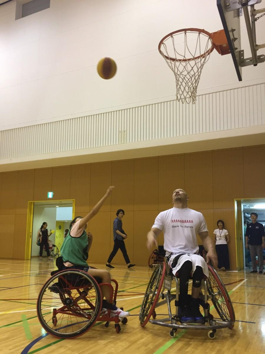 飯田橋で地域の子どもたちにパラスポーツを体験してもらうイベントを開催(画像=車いすバスケットボールの千脇貢さんからシュートを教わる児童)