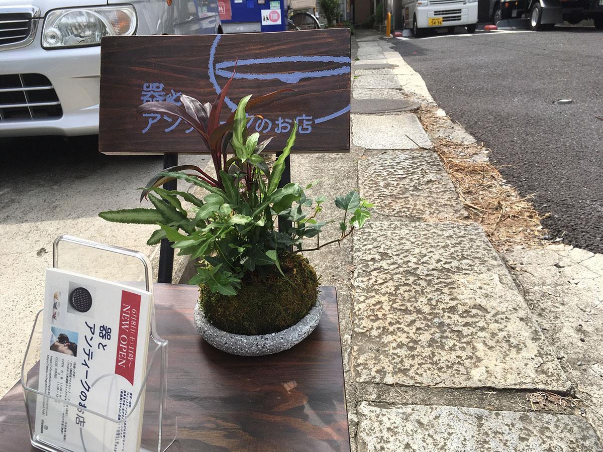 道路脇の椅子看板は路地奥の店の開店サイン